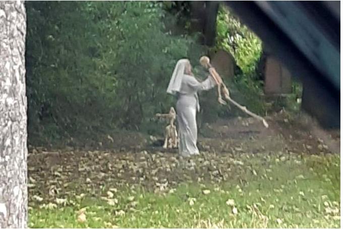 Woman dressed as nun seen dancing?with skeletons in graveyard